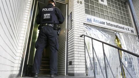 Ein Polizist steht an der Haustür zum Ansaar-Gebäude. Rechts sind die Fenster mit Folie verhangen.