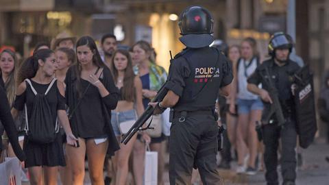"""Gesichert von schwerbewaffneten Polizisten verlassen Passanten die Flaniermeile """"La Ramblas"""" in Barcelona."""