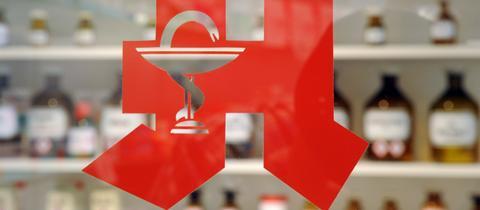 Apotheken-Logo, im Hintergrund Medikamente.