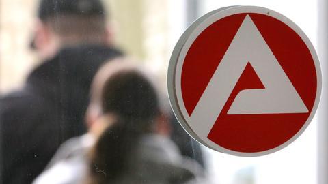 Aufkleber mit dem Logo der Abgentur für Arbeit auf einer Glasscheibe, im Hintergrund Besucher.