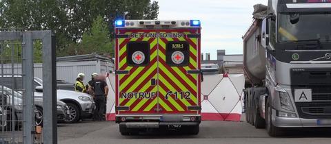 Rettungswagen und Laster auf dem Firmengelände