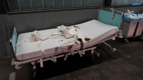 Ein Krankenhausbett, an dem an der linken Bettseite größere Brandflecken zu sehen sind