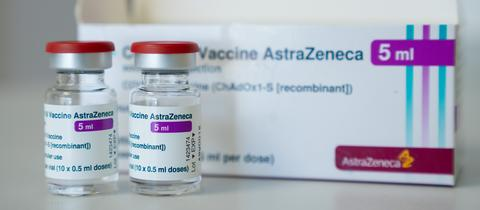 Foto des Impfstoffes AstraZeneca, der gegen Covid-19 schützen soll. Zu sehen ist die Verpackung neben zwei kleinen Fläschen mit dem Impfstoff.