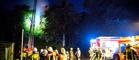 Der Atzelbergturm bei Kelkheim in Flammen, die Feuerwehr löscht