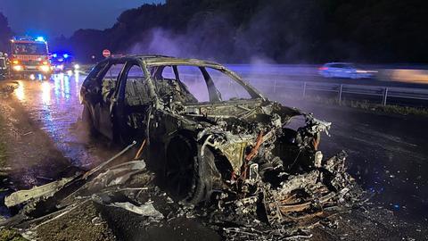 Ausgebranntes Autowrack neben Autobahn