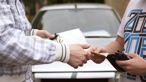 Ein Mann übergibt einem anderen Mann Autoschlüssel und -papiere gegen Geld. Es sind nur die Hände zu sehen.