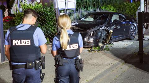 Polizisten sichern den Unfallort, wo der Sportwagen eine Laterne rammte.