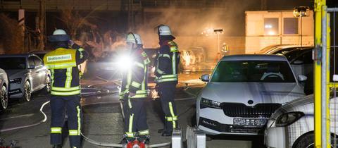 Feuerwehrmänner stehen vor verbrannten Autos
