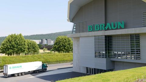 Blick auf eine Industriehalle mit der Aufschrift B.Braun. Daneben fährt auf einer Straße ein LKW mit der Aufschrift B.Braun. Im Hintergrund ist Landschaft zu sehen.