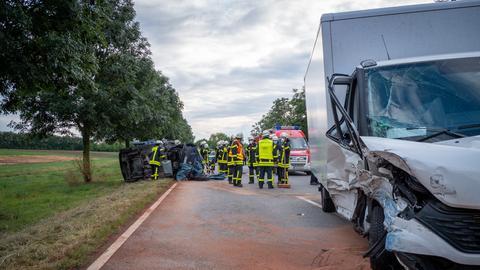 Im Vordergrund sieht man rechts die zerbeulte Front eines weißen Kleintransporters - hinten ist der Unfallgegener, ein umgestürzter blauer Pkw zu sehen.