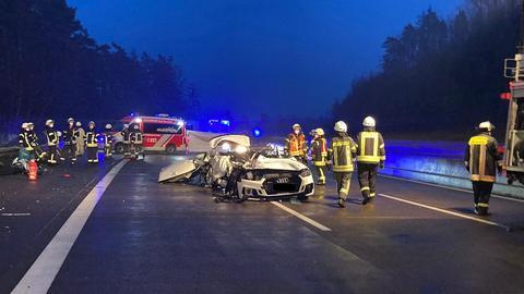 Unfallwagen auf der A4 - ein weißer Audi, das Dach ist abgetrennt. Um den Wagen stehen Einsatzkräfte der Feuerwehr.