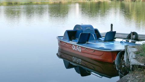 Foto eines kleinen Rettungsbootes der DLRG am Ufer eines Badesees.