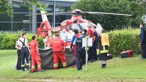 Rettungskräfte stehen an einem See, hinter ihnen ist ein Hubschrauber gelandet