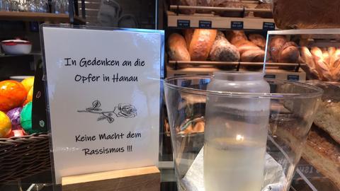Eine Hanauer Bäckerei hat eine Gedenktafel und eine Kerze für die Opfer aufgestellt.