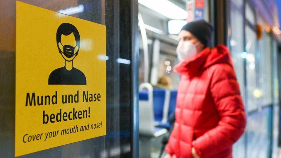 Eine Frau mit Maske wartet auf einen Zug.