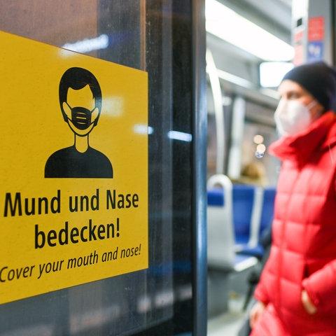 Ein Mann mit Maske steigt in einen Zug.