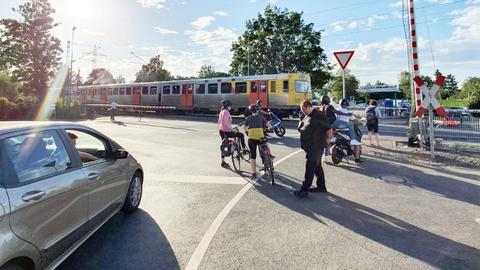Am Bahnübergang in Frankfurt-Nied fährt ein Zug bei halbgeöffneter Schranke durch