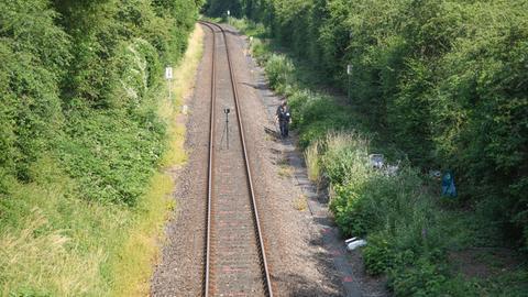 Polizisten am Rand eines eingleisigen Bahndamms.