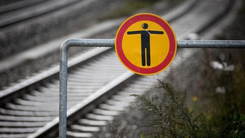 Leere Bahngleise mit einem Warnschild