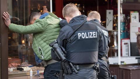 Ein Mann wird von Polizeibeamten im Frankfurter Bahnhofsviertel festgenommen