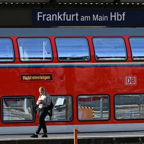 """Eine Frau steht an einem Gleis des Frankfurter Hauptbahnhofs vor einem Regionalzug, auf dem die Anzeige """"Nicht einsteigen"""" leuchtet."""