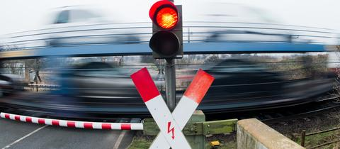 Beschrankter Bahnübergang mit vorbeifahrendem Zug