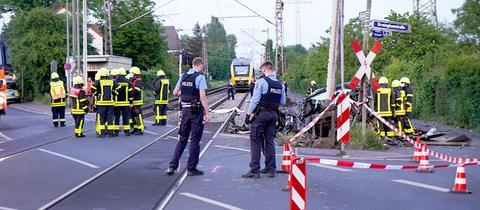 Polizisten und Rettungskräfte stehen am Bahnübergang in Frankfurt-Nied nach dem Unfall und dokumentieren das Geschehene.