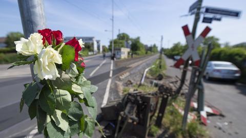 Blumen stecken am Unglücksort an einem Bahnübergang im Stadtteil Nied.