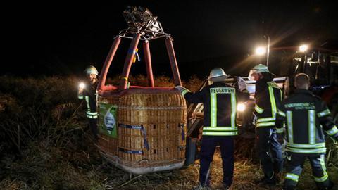Feuerwehrleute stützen den Korb eines Heißluftballons, der auf der Ladefläche eines Traktors steht