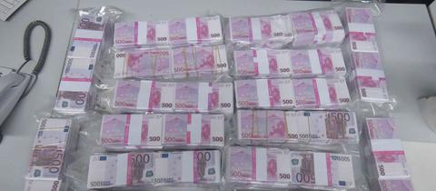500-Euro-Bündel auf einem Tisch angeordnet.