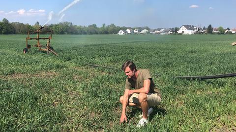 Bauer auf Feld mit Beregnungsanlage