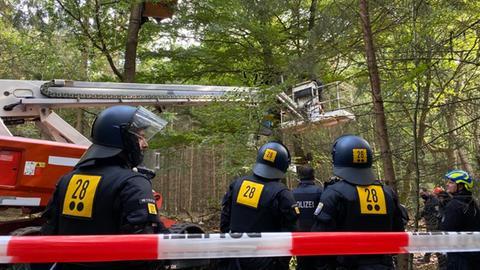 Die Polizei rückt mit einem Hubwagen gegen die Baumhäuser vor.