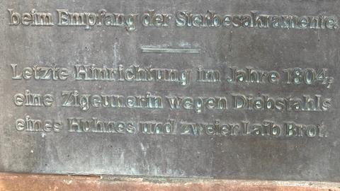 """Auf der Tafel steht: """"Letzte Hinrichtung im Jahre 1804; eine Zigeunerin wegen Diebstahls eines Huhnes und zweier Laib Brot."""""""