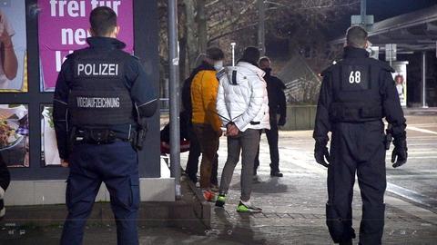 Polizisten in Bensheim mit Jugendlichen, die sie nach Autobränden festnahmen