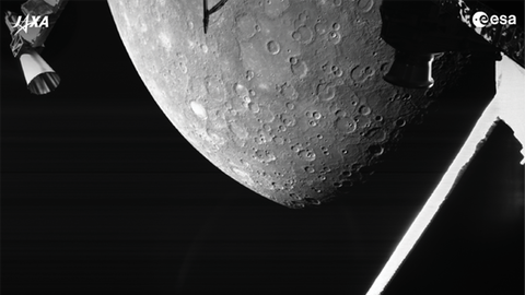 Der Planet Merkur in weiß vor schwarzem Hintergrund, im Vordergrund ist ein Teil einer Raumsonde sichtbar.
