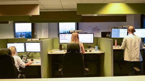 Frauen in einem Büro mit Telefon-Headsets von hinten abgebildet