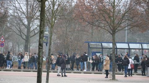 Jugendliche stehen in einer langen Reihe an einer Bushaltestelle.