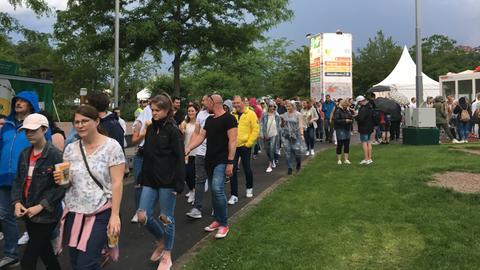Besucher des Hessentags verlassen nach dem Konzert-Abbruch das Gelände.