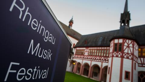 """Das Plakat """"Rheingau Musik Festival"""" steht im historischen Innenhof des Klosters."""