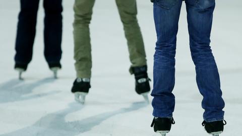 Die Beine von drei Personen, die Schlittschuhlaufen.