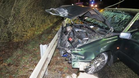 Ansicht eines völlig zerstörten grünen Autos von schräg vorne bei Nacht. Man sieht unter anderem den Motorblock.