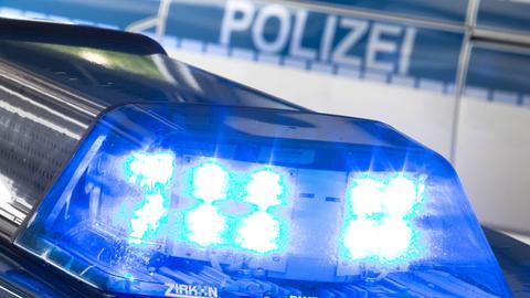 """Ein Blaulicht, im Hintergrund der Schriftzug """"Polizei""""."""