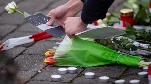 Eine Frau legt als Zeichen der Trauer eine Karte und Blumen an einem Tatort in Hanau nieder.