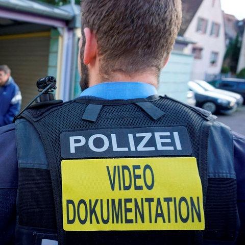 Polizist mit Body-Cam auf der Schulter und Weste mit der Aufschrift Polizei Videodokumentation