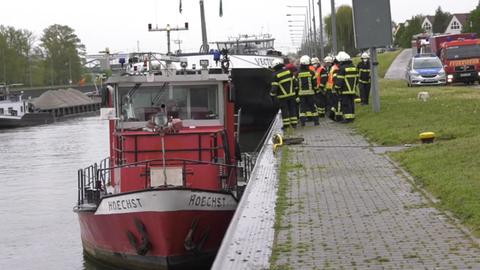 """Feuerwehrleute stehen vor dem Schiff """"Höchst"""", das am Mainufer ankert."""