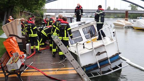Feuerwehrleute stehen auf und neben dem Boot.