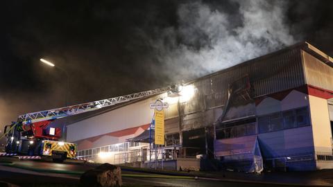 Feuerwehrleute bei Löscharbeiten an Lagerhalle
