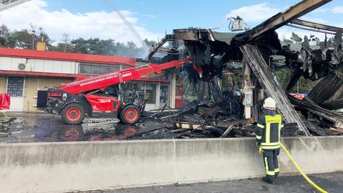 Eine Tankstelle in dunklem Schutt und schwarzer Asche. Zwei Feuerwehrleute löschen letzte Reste - einer von oben aus der Luft, einer vom Boden aus.