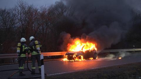 Feuerwehrleute vor brennendem Auto