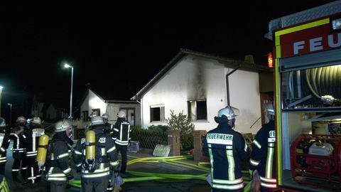 Feuerwehrleute stehen im Dunkeln vor einem Haus mit Brandspuren
